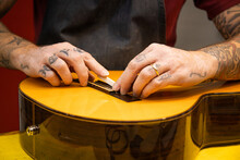 Unrecognizable Master Adjusting Guitar Saddle