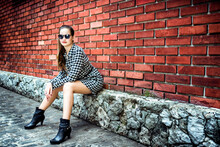 Young Girl With Plaid Blouse In Front Of A Red Brick Wall.