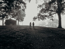 Black And White Photo Of Two Girls In Silhouette Holding Hands Between Tall Trees With Fog
