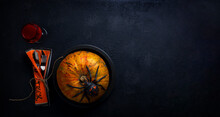 Halloween Party Table Concept With Halloween Pumpkin On Plate With A Black Scary Spider On Top, A Glass With Red Bloody Smudges And Cutlery In A Napkin On A Black Background With Copy Space. Top View.