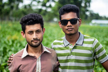 Two Handsome Boys Are Standing In The Middle Of Green Nature And One Of Them Is Wearing Sunglasses. The Background Blur.