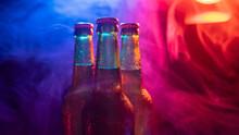 Three Bottles Of Beer In A Blue-pink Mist.