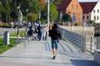 Młody mężczyzna idzie chodnikiem wzdłuż kanału we Wrocławiu.