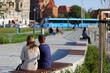 Dwie kobiety siedzą na ławkach nad rzeką Odrą we Wrocławiu.