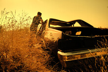 A Man  Next To The Abandoned And Brownfield Vintage Style Car Standing On Agricultural Field Covered By Yellow Plants And Grass