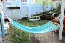 Beautiful Blue Hammock With Tassels Hanging On Log Wooden White House. Rest On Hammock With Nobody. Hammock For Relax On Backyard Outside. Iealistic Relaxation Place In Garden.
