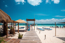 Cancun, Mexico. May 30, 2021. Wooden Pier Leading From Sand Into Sea With Moored Yachts Or Sailboat On Water Surface. Tourists Holidaying At Beach