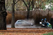Auto Und Motorrad Fährt Durch Tiefe Pfütze Nach Starkregen, Wasser Spritzt.