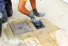 Albañil Instalando Una Llave De Paso De Agua Potable En La Acera De Una Calle. Trabajador De La Construcción Colocando Una Válvula De Paso En La Conducción Para Abastecimiento De Agua