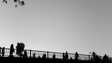 People Walking Over Trikala Bridge In Black And White.