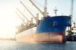 Leinwandbild Motiv Large cargo ship (bulk Carrier, 187 meters length) loading in port terminal, cranes in the background. Freight transportation, logistics, global communications, economy, business, industry