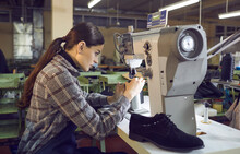 Female Worker Making New Boots At A Shoe Factory Workshop. Serious Concentrated Young Woman Sitting At A Table And Working On An Industrial Shoe Sewing Machine. Footwear Manufacturing Industry Concept