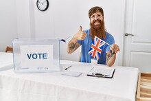 Caucasian Man With Long Beard At Political Campaign Election Holding Uk Flag Smiling Happy And Positive, Thumb Up Doing Excellent And Approval Sign