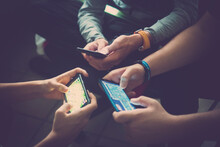Close Up Of Hands Of Three Teenager Friends Addicted To Technology Playing With Smartphones Together. Teenage Boys Using Mobile Phones For Social Networking And Leisure Activities.