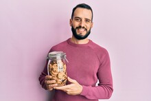 Young Man With Beard Holding Jar Of Chocolate Chips Cookies Looking Positive And Happy Standing And Smiling With A Confident Smile Showing Teeth
