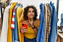 Young Hispanic Woman Searching Clothes On Clothing Rack Using Smartphone Thinking Concentrated About Doubt With Finger On Chin And Looking Up Wondering