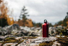 Red Hiking Bottle Stands In Autumn Yellow Forest