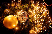 Christmas Tree With Gold Ball And Bokeh Lights Background. Xmas Abstract Close Up With Glowing Decorations Outdoors.