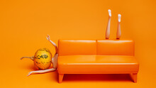 Doll With A Pumpkin Head Fallen Behind An Orange Leather Sofa On Orange Background. Creative Halloween Party Concept. Morning Hangover Idea. Minimal Fashion Aesthetic Art.
