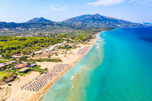 Top View Aerial Drone Photo Of Banana Beach With Beautiful Turquoise Water, Sea Waves And Red Umbrellas. Vacation Travel Background. Ionian Sea, Zakynthos Island, Greece
