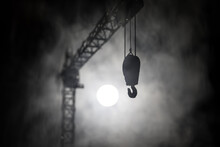 Abstract Industrial Background With Construction Crane Silhouette Over Amazing Night Sky With Fog And Backlight. Tower Crane Against The Foggy Sky At Night.