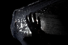 Abstract Silhouette Hands Streching And Pushing Half Transparent Fabric With Tiny Holes And Light In The Background