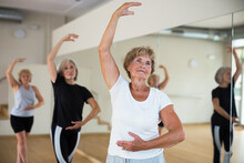 Positive Elderly Woman Practicing Ballet Dance Moves During Group Class In Choreographic Studio.