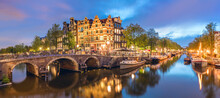 Amsterdam, Netherlands. Panorama Of The Historic City Center Of Amsterdam. Traditional Houses And Bridges Of Amsterdam Small Town. A Romantic Evening And A Bright Reflection Of Houses In The Water.
