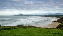 Green Grassy Cliffs Drop Down To The Ocean Coast And A Large Beautiful Sandy Beach