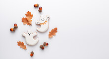 Halloween Gingerbread Cookies On Stone Background. Two Cute Ghosts On A White Background With Oak Leaves And Acorns. Copy Space