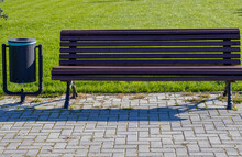 Public Park Bench And Trash Bin Near. Green Grass Background, Walkside Concept: Keed Clean, Eco Environment, Relax Autumn, Summer