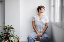 Woman Looking Through Window While Sitting By Plants At Home