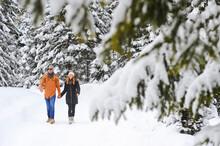Man And Woman Enjoying Leisure Time While Walking On Snow During Winter