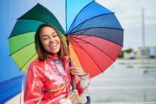 Happy Woman Wearing Raincoat Holding Multi Colored Umbrella During Rainy Season