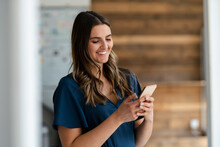 Smiling Businesswoman Using Mobile Phone In Office