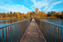 A Bridge Leading To The Center Of The Lake Above The Water With Metal Railings On The Background