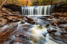 Flowing Silky Cascading Waters With  Colorful Autumn Foliage Background  On The  Woods In Ricketts Glen Pennsylvania