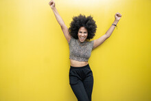 Excited Young Afro Woman With Arms Raised In Front Of Yellow Wall