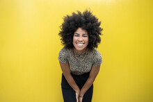 Afro Woman Smiling In Front Of Yellow Wall