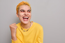 Pretty Optimistic Punk Girl Feels Like Winner Celebrates Success Clenches Fist Looks Happily Away Wears Casual Yellow Jumper Isolated On Grey Background Blank Copy Space Belongs To Youth Subculture