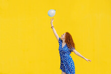 Carefree Redhead Woman Playing With Balloon In Front Of Yellow Wall
