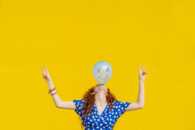 Carefree Woman Balancing Balloon With Anthropomorphic Smiley Face In Front Of Yellow Wall