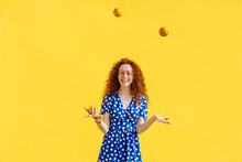 Carefree Woman Juggling Orange Fruits In Front Of Yellow Wall