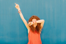 Smiling Woman Covering Eyes While Standing In Front Of Blue Wall