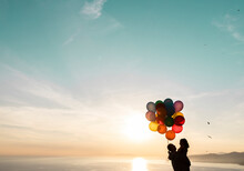 Man Carrying Daughter Holding Colorful Balloons During Sunset