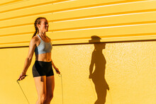 Smiling Sportswoman Jumping While Using Skipping Rope By Yellow Wall