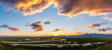 Bayinbuluke Grassland And Winding River Natural Scenery In Xinjiang At Sunset,China.The Winding River Is On The Green Grassland.
