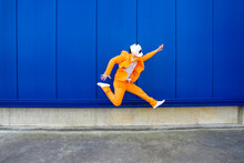 Man Wearing Vibrant Orange Suit And Panda Mask Jumping Against Blue Wall