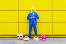 Man Wearing Vibrant Blue Suit And Bird Mask Standing In Front Of Yellow Wall With Various Animal Masks