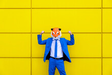 Man Wearing Vibrant Blue Suit And Tiger Mask Flexing In Front Of Yellow Wall